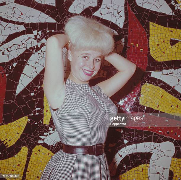 English actress Barbara Windsor posed in front of a mosaic panel in London in 1964
