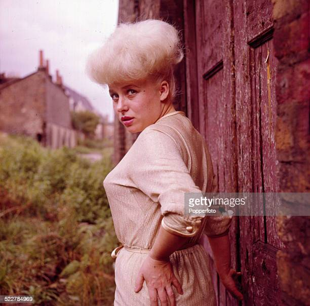 English actress Barbara Windsor posed beside a derelict building in London in 1964