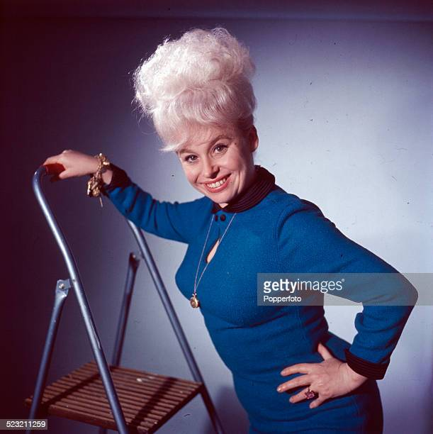 English actress Barbara Windsor posed wearing a blue dress whilst standing on a ladder in 1963