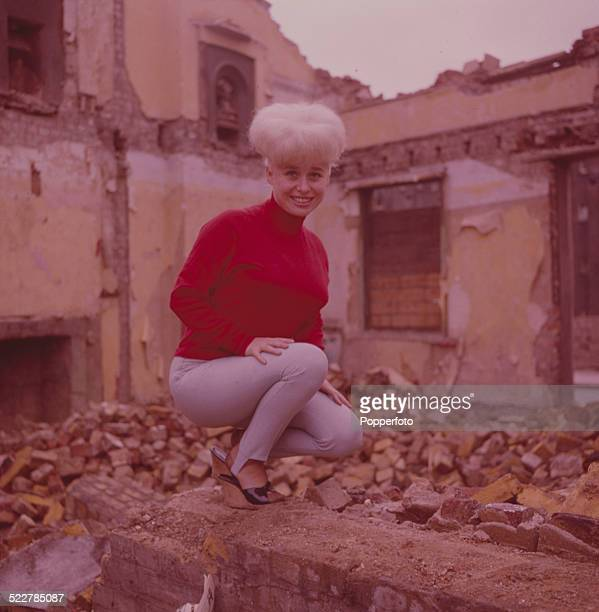 English actress Barbara Windsor posed wearing a red jumper beside a demolished building in London in 1964