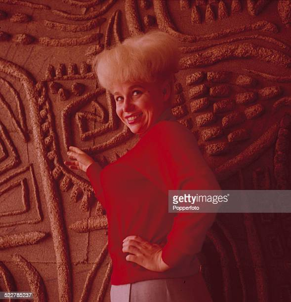English actress Barbara Windsor posed wearing a red jumper beside a carved wood panel in London in 1964