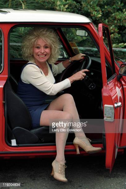English actress Barbara Windsor poses in a red mini during a photocall circa 1980