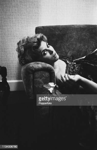English actress Billie Whitelaw pictured lying on a sofa in an apartment in England in December 1963.