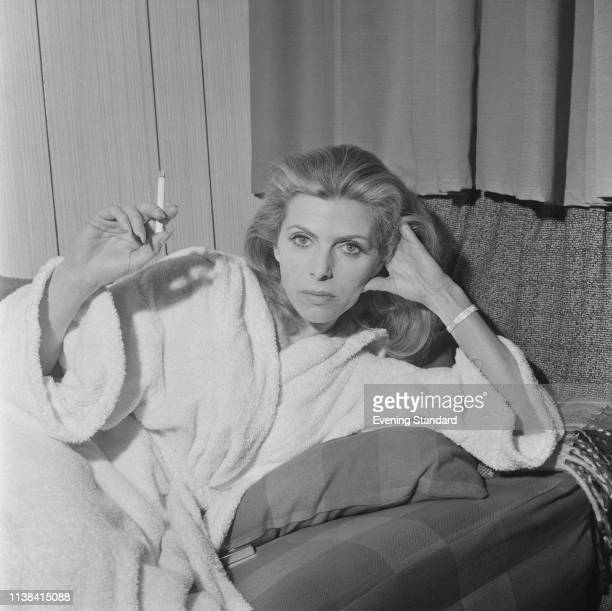 English actress Billie Whitelaw wearing a bathrobe as she smokes a cigarette, UK, 19th June 1969.