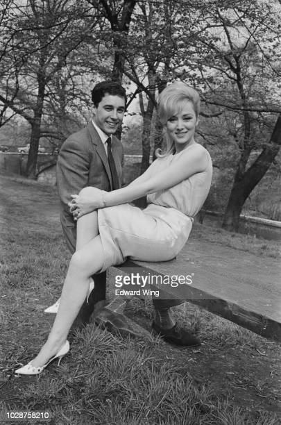 English actress Carole Lesley pictured seated on a riverside bench with her fiance Michael Dalling in England on 27th April 1963