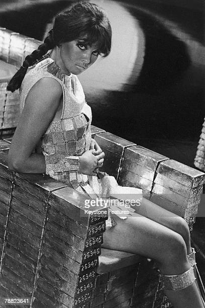 English actress Caroline Munro sitting on a throne of fake gold ingots in a promotional still for 'Casino Royale' directed by Val Guest et al January...