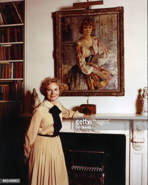 English actress Dame Anna Neagle circa 1980 Behind her is a portrait of Neagle as a young woman
