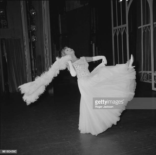 English actress Dame Anna Neagle dancing in her Norman Hartnell gown between performances of the musical 'Charlie Girl' at the Adelphi Theatre in...