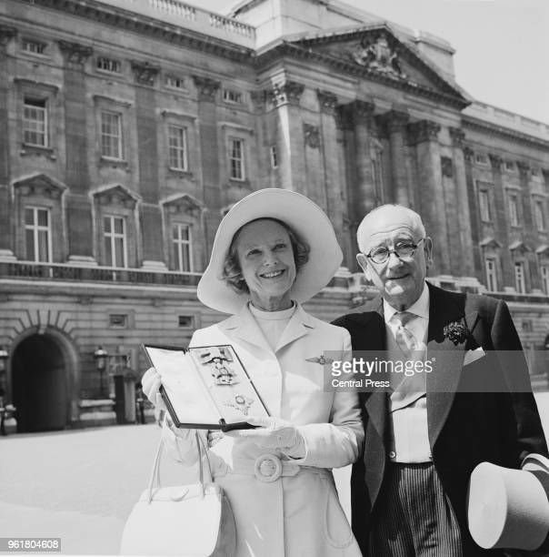 English actress Dame Anna Neagle leaves Buckingham Palace in London with her husband director Herbert Wilcox after receiving her DBE from the Queen...