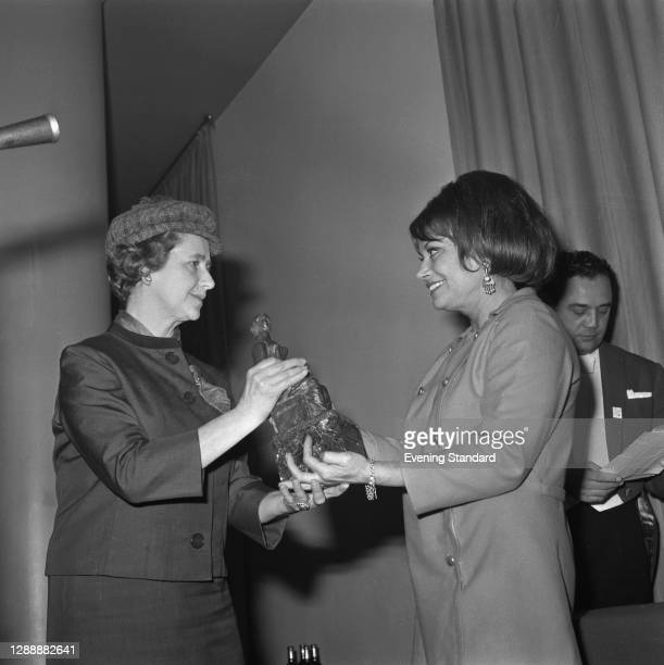 English actress Dame Peggy Ashcroft presents the Best Actress award to French actress Lila Kedrova at the Evening Standard Theatre Awards for 1967,...