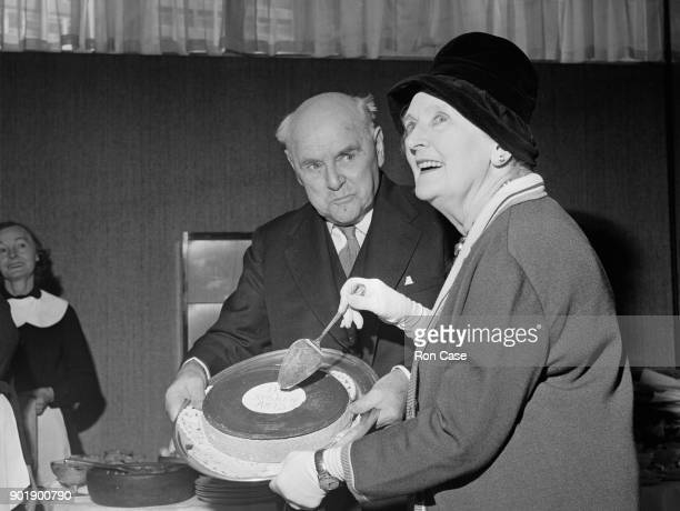 English actress Dame Sybil Thorndike and her husband Sir Lewis Casson cut the cake at a Thorndike family reunion at a restaurant in London 9th March...