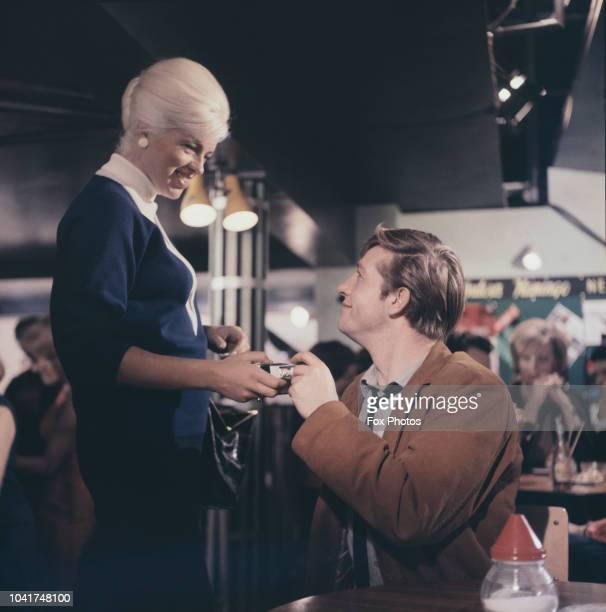 English actress Diana Dors and actor Alfred Lynch filming a scene for the movie 'West 11', circa 1963. The film is directed by Michael Winner.
