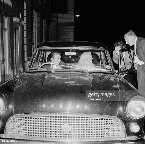 English actress Diana Dors and her husband English-American actor and comedian Richard Dawson talking to friends from their car, 1958.
