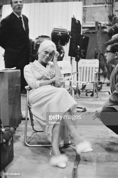 English actress Diana Dors pictured seated in a chair on set during shooting of the film West 11 in London on 29th January 1963
