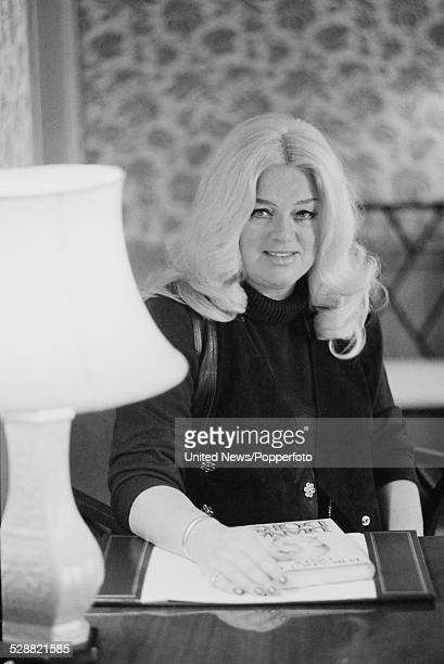 English actress Diana Dors pictured sitting at a desk on the publication day of her autobiography 'For Adults Only' in London on 14th February 1978