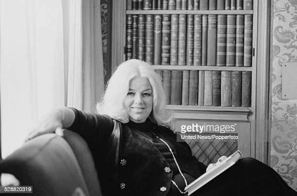 English actress Diana Dors pictured sitting on a chair in a library in London on 14th February 1978