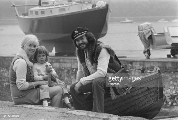 English actress Diana Dors pictured with her husband actor Alan Lake and son Jason seated on a boat slipway in England on 11th May 1972