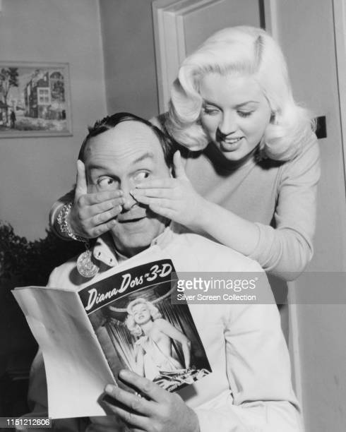 English actress Diana Dors surprises actor Maurice Denham who is reading the 'Diana Dors in 3D' booklet circa 1950