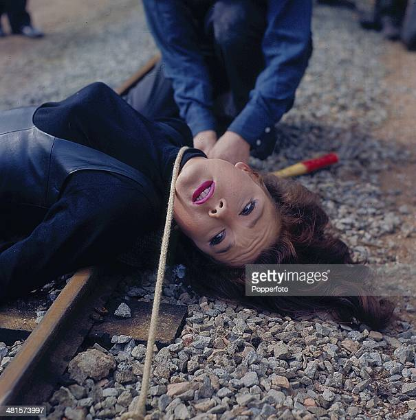 1968 English actress Diana Rigg as 'Emma Peel' is tied to a miniature train track in a scene from the television series 'The Avengers' in 1968