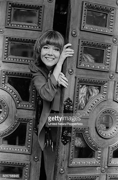 English actress Diana Rigg emerges from the doors of the Phoenix Theatre in London during a West End run of the Tom Stoppard play Night and Day on...
