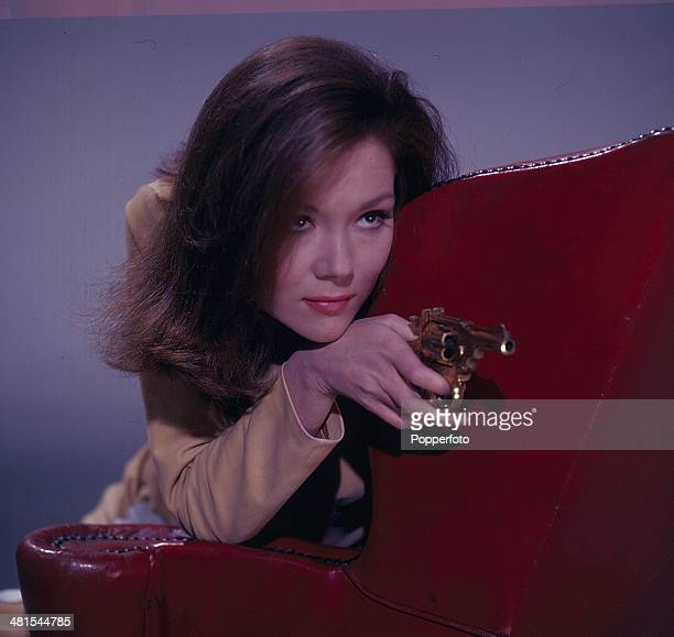 English actress Diana Rigg in her role as 'Emma Peel' from the television series 'The Avengers' crouches behind a chair whilst holding a gun in 1968.
