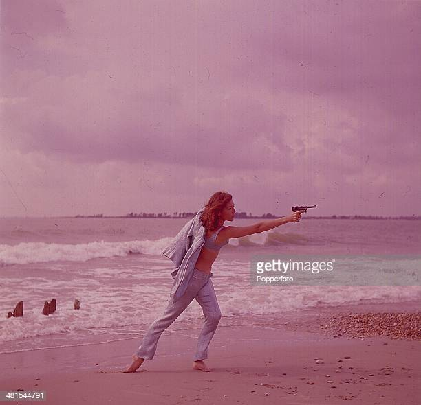 1968 English actress Diana Rigg in her role as 'Emma Peel' from the television series 'The Avengers' holds a gun on a beach in 1968