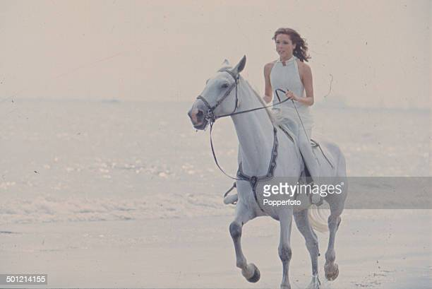 English actress Diana Rigg in her role as 'Emma Peel' from the television series 'The Avengers' rides a horse on Camber Sands England in 1967