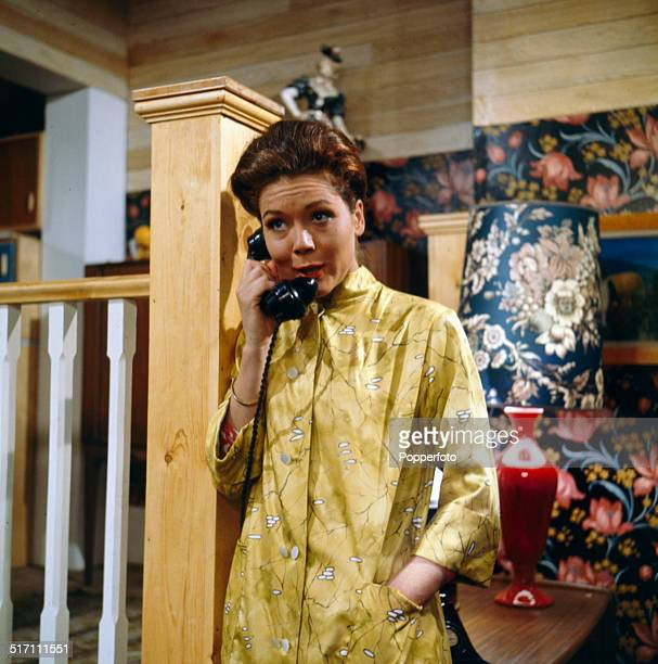 English actress Diana Rigg pictured holding a telephone receiver in a scene from the television drama 'The Hot House' in 1964