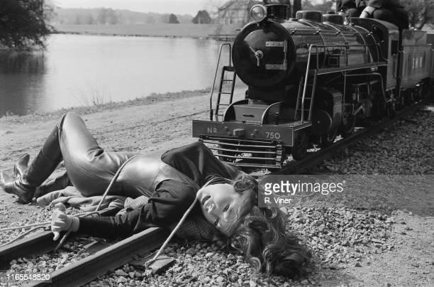 English actress Diana Rigg tied to the rail of a train filming a scene of television series 'The Avengers' UK 4th April 1965