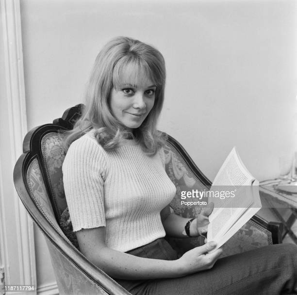 English actress Elaine Taylor reading a book at home in July 1966
