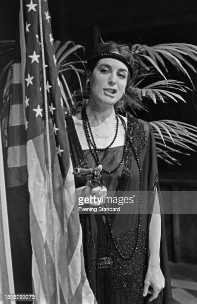 English actress Eleanor Bron poses in 1920s costume with a prop gun and a US flag, UK, 17th November 1973.