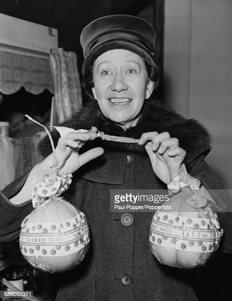 English actress Flora Robson holds two Italian cheeses as she opens the United Charities Fair at Grosvenor House London November 9th 1959