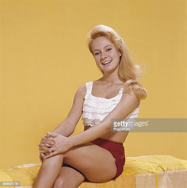 English actress Francesca Annis pictured wearing a white peasant style cropped top and red shorts in 1962