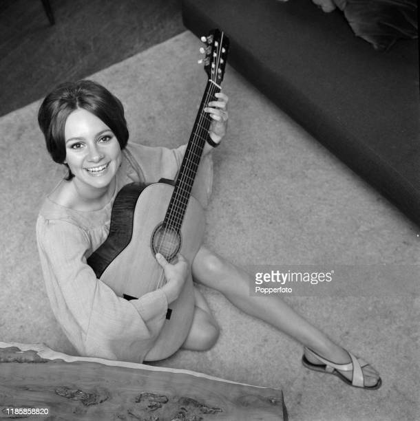 English actress Francesca Annis posed at home playing an acoustic guitar in September 1966