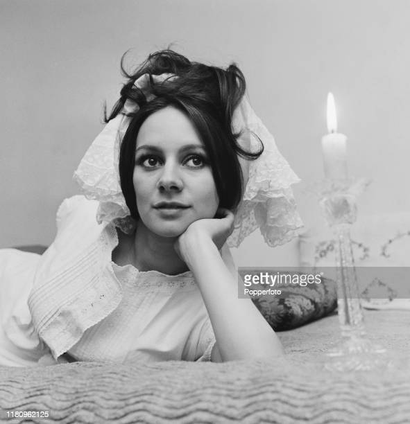 English actress Francesca Annis posed on a bed wearing a lace scarf in her hair at home in December 1966