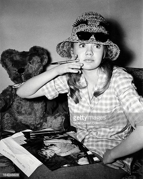English actress Hayley Mills autographing photographs for members of her fan club circa 1964