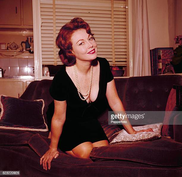 English actress Hazel Court posed wearing a black dress and pearl necklace in 1964