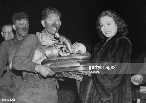 English actress Hazel Court presents the Daily Mail National Speedway Trophy to Jack Parker captain of the winning Belle Vue team from Manchester...