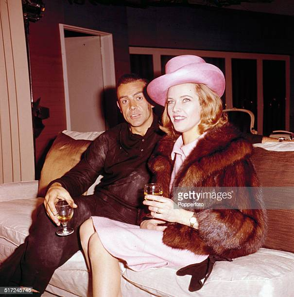 English actress Honor Blackman and Scottish actor Sean Connery sit together on a couch with drinks during a break in the filming of the James Bond...