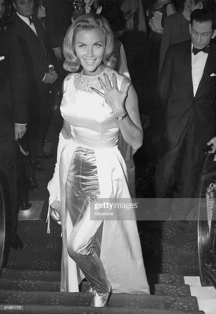 English actress Honor Blackman attends the premiere of the latest Bond film 'Goldfinger' at the Odeon, Leicester Square, 18th September 1964. One of her fingers has been painted gold in honour of the film's title.