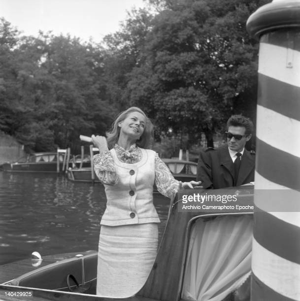 English actress Honor Blackman brushing her hair with Maurice Kaufmann on a water taxi Lido Venice 1965