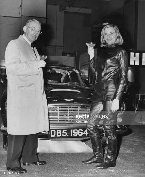 English actress Honor Blackman of TV's 'The Avengers' and Aston Martin chairman David Brown with the new Aston Martin DB5 hard top at the Motor Show...