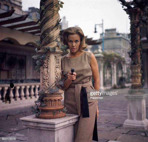 English actress Honor Blackman pictured in character as Cathy Gale pointing a gun in a scene from the television series The Avengers in 1964