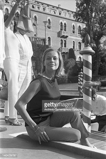 English actress Honor Blackman sitting on a floor and posing for the photographers Lido Venice 1965