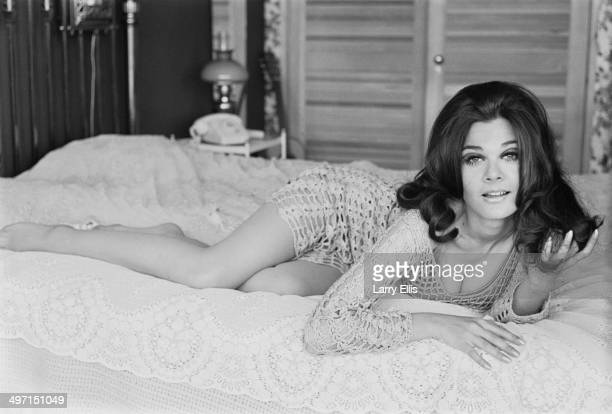 English actress Imogen Hassall lying on a bed in a lace mini dress 11th June 1968
