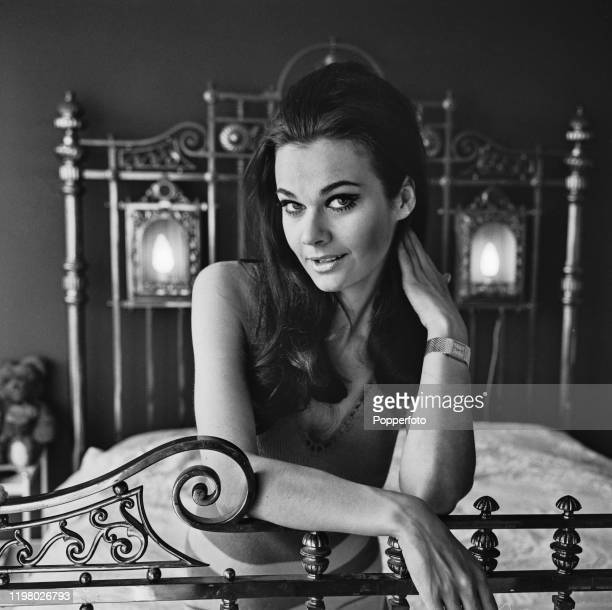 English actress Imogen Hassall posed on a brass double bed at home in May 1968