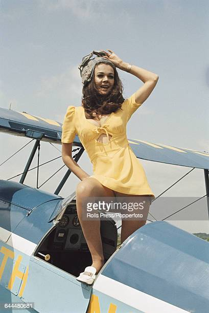 English actress Imogen Hassall who appears in the film 'Carry On Loving' pictured wearing a yellow mini dress as she stands in the cockpit of a...