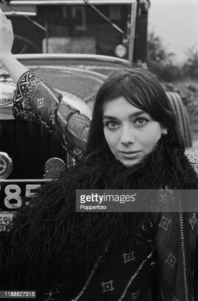 English actress Jacqueline Pearce posed in front of a vintage car in August 1966