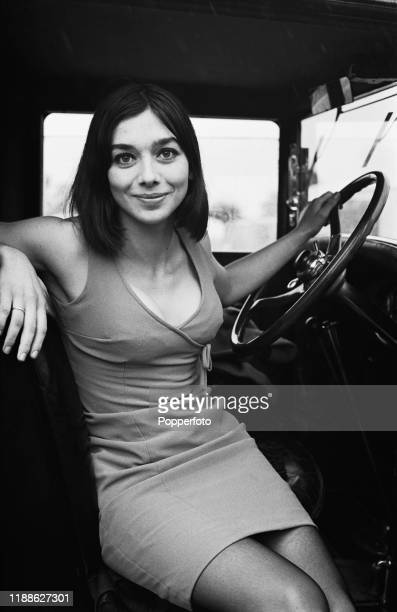 English actress Jacqueline Pearce posed seated in the driver's seat of a vintage car in August 1966