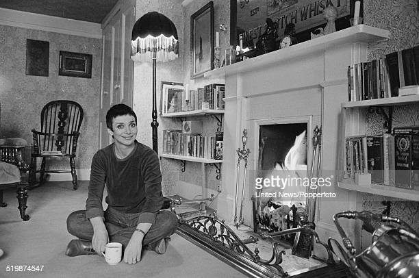 English actress Jacqueline Pearce posed sitting on the floor of a living room beside a fireplace in London on 25th January 1980